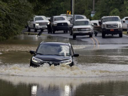 Motorists try to navigate deep water flowing over a road in Walker, La., Monday, Aug. 15, 2016. Although some flood waters have receded roads continue to be difficult to pass with private vehicles. (AP Photo/Max Becherer)