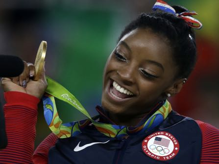 United States' Simone Biles displays her gold medal for floor during the artistic gymnastics women's apparatus final at the 2016 Summer Olympics in Rio de Janeiro, Brazil, Tuesday, Aug. 16, 2016. (AP Photo/Rebecca Blackwell)