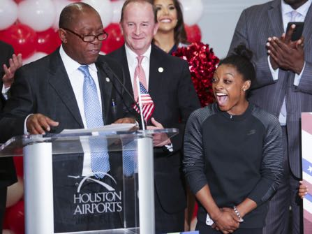 Gymnast Simone Biles reacts as Houston Mayor Sylvester Turner declares Wednesday, Aug. 24, 2016, to be Simone Biles Day, as she is welcomed home at George Bush Intercontinental Airport in Houston, Texas, after winning four gold medals and a bronze at the Olympics in Rio de Janeiro. (Michael Ciaglo/Houston Chronicle via AP)