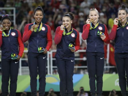 U.S. gymnasts, left to right, Simone Biles, Gabrielle Douglas, Lauren Hernandez, Madison Kocian and Aly Raisman hold their gold medals during the medal ceremony for the artistic gymnastics women's team at the 2016 Summer Olympics in Rio de Janeiro, Brazil, Tuesday, Aug. 9, 2016. (AP Photo/Julio Cortez)