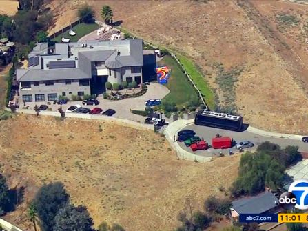 This still frame from aerial video provided by KABC-TV shows the home of entertainer Chris Brown with police vehicles outside, in the Tarzana area of Los Angeles Tuesday, Aug. 30, 32016. Authorities waited for a search warrant outside Brown's Los Angeles home Tuesday after a getting a woman's call for help, officials said. Inside, the entertainer, who has a history of legal problems, posted videos to social media declaring his innocence. (KABC-TV via AP) MANDATORY CREDIT TV OUT