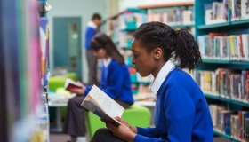 High School students sitting and reading book in library