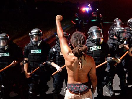 A protester stands with his left arm extended and fist clenched in front of a line of police officers in Charlotte, N.C. on Tuesday, Sept. 20, 2016. Authorities used tear gas to disperse protesters in an overnight demonstration that broke out Tuesday after Keith Lamont Scott was fatally shot by an officer at an apartment complex. (Jeff Siner/The Charlotte Observer via AP)