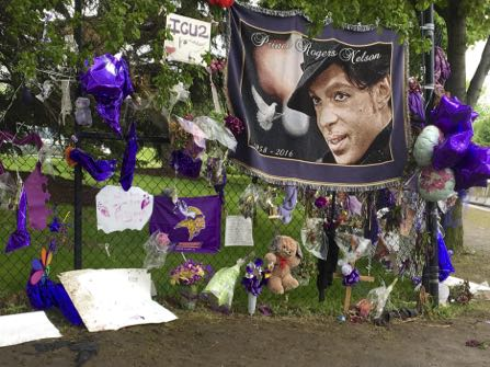 HOLD FOR STORY BY STEVE KARNOWSKI - FILE - In this May 11, 2016, file photo, items left by fans at a memorial for Prince hang from a fence outside the musician's Paisley Park estate in Chanhassen, Minn. Work to settle the estate of the late rock superstar is moving forward, though a closed hearing is expected this week to resolve an undisclosed dispute between the likely heirs and the trust company that's managing the estate. Prince died of an accidental painkiller overdose in April. (AP Photo/Jeff Baenen, File)