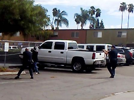 "In this Tuesday, Sept. 27, 2016 frame from video provided by the El Cajon Police Department, a man, second from left, faces police officers in El Cajon, Calif. The man reportedly acting erratically at a strip mall in suburban San Diego was shot and killed by police after pulling an object from his pocket, pointing it at officers and assuming a ""shooting stance,"" authorities said. Some protesters claimed the man was shot with his hands raised, but police disputed that and produced the frame from cellphone video taken by a witness that appeared to show the man in the ""shooting stance"" as two officers approached with weapons drawn. (El Cajon Police Department via AP)"