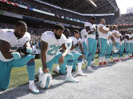 From left, Miami Dolphins' Jelani Jenkins, Arian Foster, Michael Thomas, and Kenny Stills, kneel during the singing of the national anthem before an NFL football game against the Seattle Seahawks, Sunday, Sept. 11, 2016, in Seattle. (AP Photo/Stephen Brashear)