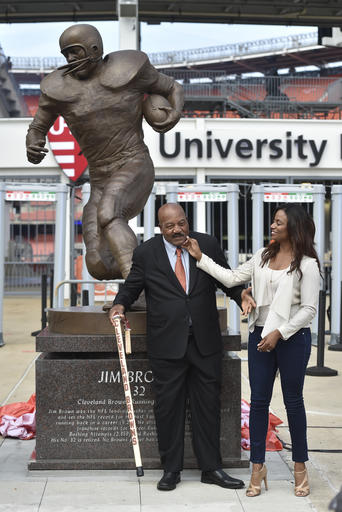 Cleveland Browns Pro Football Hall of Famer Jim Brown, center, and his wife Monique, right, is honored with a ceremony and statue outside FirstEnergy Stadium before an NFL football game against the Baltimore Ravens, Sunday, Sept. 18, 2016, in Cleveland. (AP Photo/David Richard)