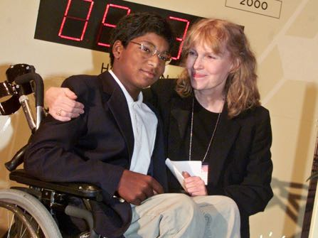 HOLD FOR STORY CONFIRMATION - FILE - In this Sept. 27, 2000 file photo, actress Mia Farrow puts her arm around her adopted son Thaddeus as they participate in the global summit on polio eradication at United Nations headquarters. Farrow, who suffered from the disease as a child, and her 12-year-old son who is paralyzed by it, joined U.N. Secretary General Kofi Annan in starting a clock to countdown the number of polio cases until 2005. (AP Photo/Richard Drew, File)