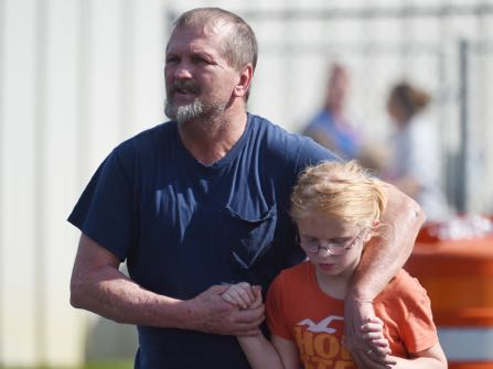 Joey Taylor walks with his daughter Josie Taylor after picking her up at Oakdale Baptist Church on Wednesday, Sept. 28, 2016, in Townville, S.C. Students were evacuated to the church following a shooting at Townville Elementary School. A teenager opened fire at the South Carolina elementary school Wednesday. (AP Photo/Rainier Ehrhardt)