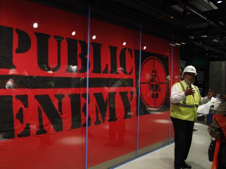 Museum Director Lonnie Bunch, second to the right, stands in-front of an art piece representing hip-hop group Public Enemy within Smithsonian's National Museum of African American History and Culture, Monday, July 18, 2016, in Washington. Bunch lead the media tour and said that the museum will be able to hold a capacity of 15,000 people per day. The museum's grand opening will be on Sept. 24. (AP Photo/Paul Holston)