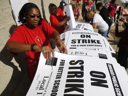 Retired Chicago school teacher Patricia Lofton counts through a stack of picket sign for Chicago Teachers Union members to pick up Monday, Oct. 10, 2016, in Chicago. Negotiators for the union and Chicago Public Schools continue to meet in an effort to reach a contract and avert a threatened teachers' strike. (AP Photo/Charles Rex Arbogast)