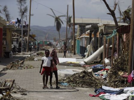 Girls make their way down a street littered with debris left by Hurricane Matthew in Les Anglais, Haiti, Monday, Oct. 10, 2016. Nearly a week after the storm smashed into southwestern Haiti, some communities along the southern coast have yet to receive any assistance, leaving residents who have lost their homes and virtually all of their belongings struggling to find shelter and potable water. (AP Photo/Rebecca Blackwell)