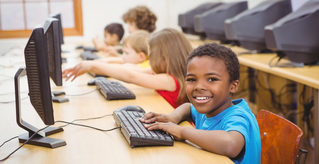 Smiling student using a computer at the elementary school