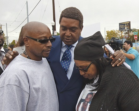 Attorney John Burris, center, comforts Robert and Deborah Mann, family members of Joseph Mann, who was killed by Sacramento Police in July, after a news conference Monday, Oct. 3, 2016, in Sacramento, Calif.  The Mann family is demanding that the officers involved in shooting of Joseph Mann, 50, be charged with murder and that the U.S. Department of Justice open a civil rights investigation of the Sacramento Police Department. (AP Photo/Rich Pedroncelli)