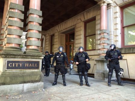 Portland police stand guard outside of City Hall in Portland, Ore., Wednesday, Oct. 12, 2016. The Portland City Council approved a new police contract in a conference room that was blocked off from the general public because of protests that led to arrests. (Brad Schmidt/The Oregonian via AP)