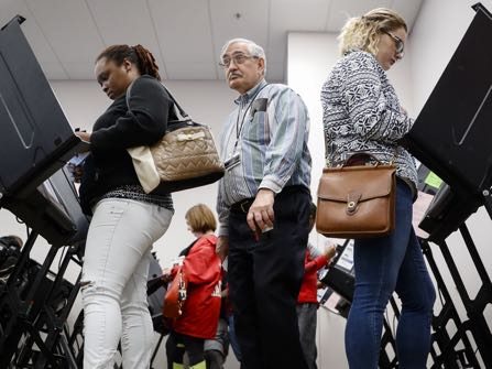 Polling worker Greg Caplinger, of Columbus, Ohio, center, passes between early voters at the Franklin County Board of Elections, Monday, Nov. 7, 2016, in Columbus, Ohio. Heavy turnout has caused long lines as voters take advantage of their last opportunity to vote before election day. (AP Photo/John Minchillo)