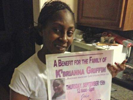 Tamika Robinson of Detroit holds a poster with a picture of her daughter, K'Brianna Griffin, Nov. 30, 2016 in Detroit, Mich. K'Brianna was killed in September when she came in contact with a downed power line in a friend's yard. Staff at the Michigan Public Service Commission are recommending that the city of Detroit remove miles of obsolete, abandoned overhead wires. (AP Photo/Corey Williams)