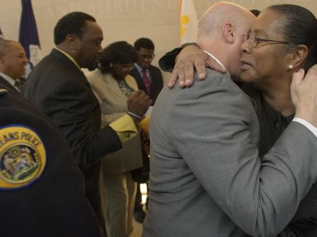 New Orleans Mayor Mitch Landrieu hugs jackie Madison Brown, whose brother Ronald Madison was killed by New Orleans Police on Danziger Bridge after Hurricane Katrina in 2005, after the mayor held a press conference to announce the settlements in the civil rights cases stemming from several New Orleans Police Department-involved incidents surrounding Hurricane Katrina at Xavier University's St. Katharine Drexel Chapel in New Orleans, La. Monday, Dec. 19, 2016. The city said it will pay out $13.3 million to 17 plaintiffs.