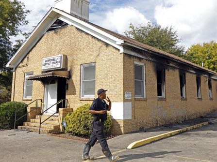 "FILE-In this Wednesday, Nov. 2, 2016 file photoA state fire marshal investigates the fire damaged Hopewell M.B. Baptist Church in Greenville, Miss., Wednesday, Nov. 2, 2016. ""Vote Trump"" was spray-painted on an outside wall of the black member church. Fire Chief Ruben Brown tells The Associated Press that firefighters found flames and smoke pouring from the sanctuary of the church just after 9 p.m. Tuesday. (AP Photo/Rogelio V. Solis, File)"