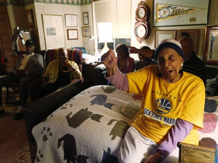 In this May 27, 2015 photo, Golden State Warriors fan Helen Brooks, better known as Sweetie, reacts as she watches an NBA playoff basketball game between the Warriors and the Houston Rockets on television with family and friends in Hayward, Calif. Brooks, a 107-year-old Northern California woman who gained fame very late in life as an avid and gregarious fan of the Warriors, died Thursday Dec. 22, 2016. (Josie Lepe/Bay Area News Group via AP)