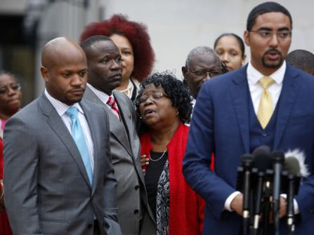 FILE- Judy Scott, center, Walter Scott's mother, is comforted by her son Rodney Scott, as the family attorneys, Chris Stewart, left, and Justin Bamberg, right, hold a press conference after the mistrial was declared for the Michael Slager trial Monday Dec. 5, 2016, in Charleston, S.C. Former patrolman, Slager, is charged with murder in the shooting death of Walter Scott last year. (AP Photo/Mic Smith, File)