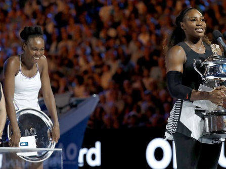 United States' Serena Williams holding her trophy at right, addresses the spectators, in front of her sister Venus, second from left, and former champion Hana Mandlikova, after her women's singles final victory, at the Australian Open tennis championships in Melbourne, Australia, Saturday, Jan. 28, 2017. (AP Photo/Kin Cheung)