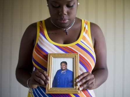 """FILE-In this Friday, June 19, 2015 file photo, Najee Washington holds a photo of her grandmother Ethel Lance, one of the nine people killed in Wednesday's shooting at Emanuel AME Church, by Dylan Roof, as she poses for a portrait outside her home, in Charleston, S.C. """"She cared for everyone.During Dylan Roof's sentencing for friends and family members walked up to the witness stand and testified about the nine black church members gunned down during a Bible study. The testimony came during the sentencing phase of Dylann Roof's death penalty trial. (AP Photo/David Goldman, File)"""