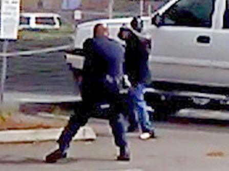 FILE - In this Tuesday, Sept. 27, 2016 file frame from bystander video provided by the El Cajon Police Department, Alfred Olongo, right, is seen pointing what was later determined to be a bulky electronic cigarette device at El Cajon, Calif., police officer Richard Gonsalves during a confrontation at an El Cajon strip mall. Moments later Olongo was shot and killed. San Diego County District Attorney Bonnie Damais announced Tuesday, Jan. 10, 2017 that no criminal charges will be filed against Gonsalves. (El Cajon Police Department/San Diego County District Attorney's Office via AP, File)