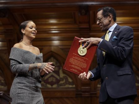 Singer Rihanna, left, is presented with the 2017 Harvard University Humanitarian of the Year Award by Allen Counter, director of the Harvard Foundation, right, during ceremonies at the school, Tuesday, Feb. 28, 2017, in Cambridge, Mass. (AP Photo/Steven Senne)